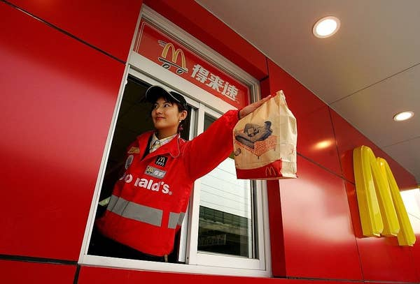 A McDonald's employee hands out food as she waits on customers at their new drive-thru facility on January 19, 2007 in Beijing, China