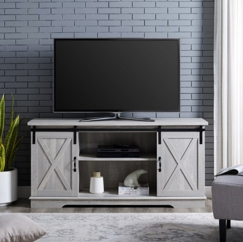 Light gray rustic TV stand with two barn door cabinets and shelving in middle