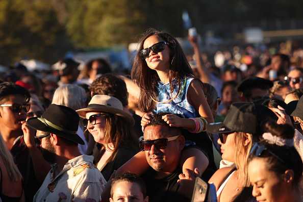 A girl sitting on a man's shoulders enjoying the concert