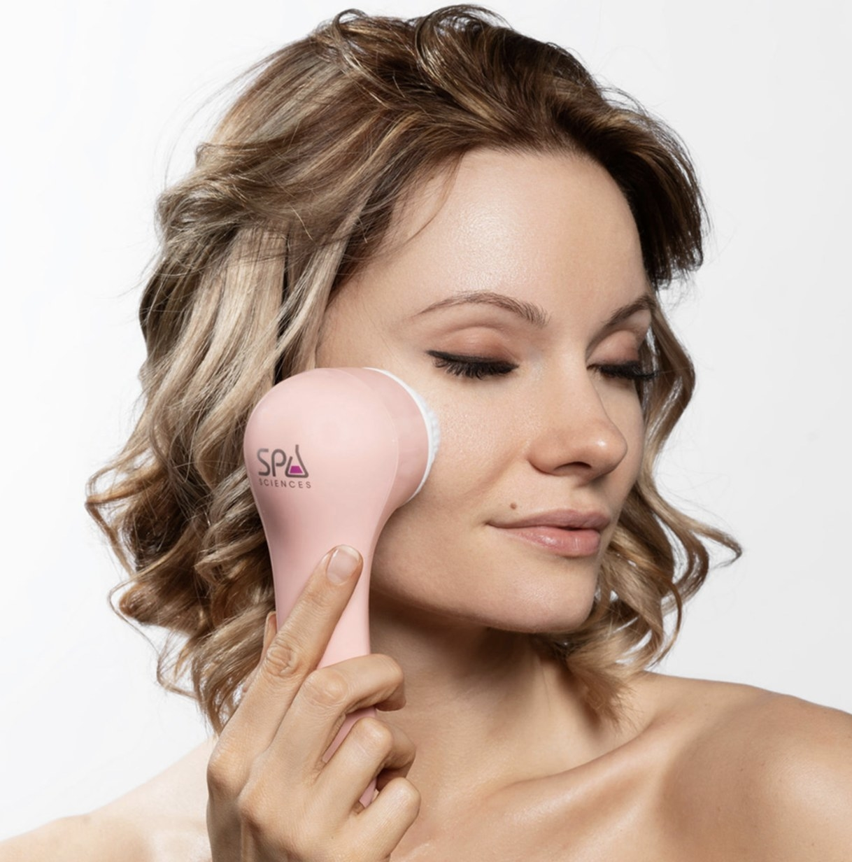 Person is using a cleansing brush on their cheek