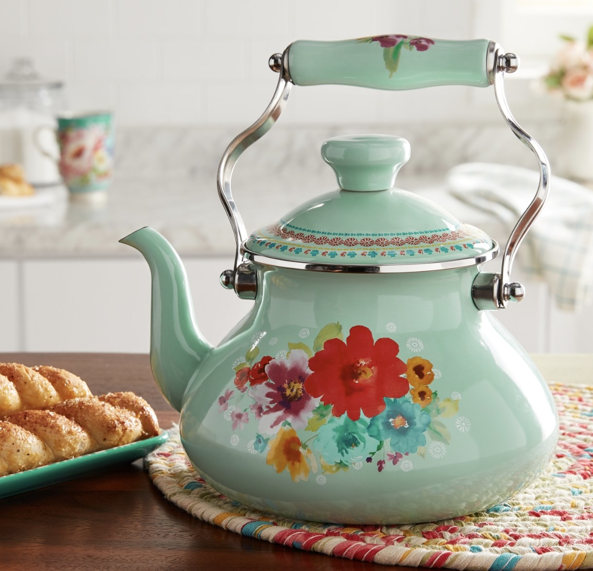 A light blue tea kettle with a floral design