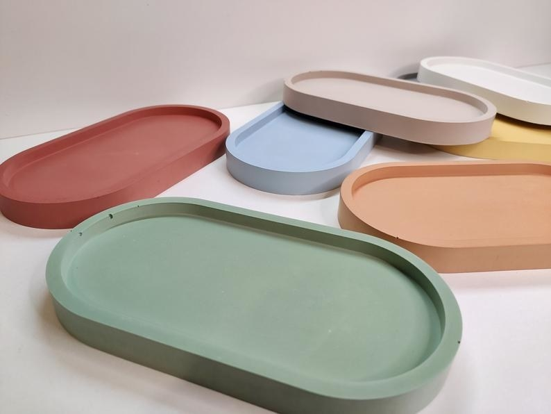 Seven of the concrete oval trays in green, red, orange, blue, beige, white, and yellow