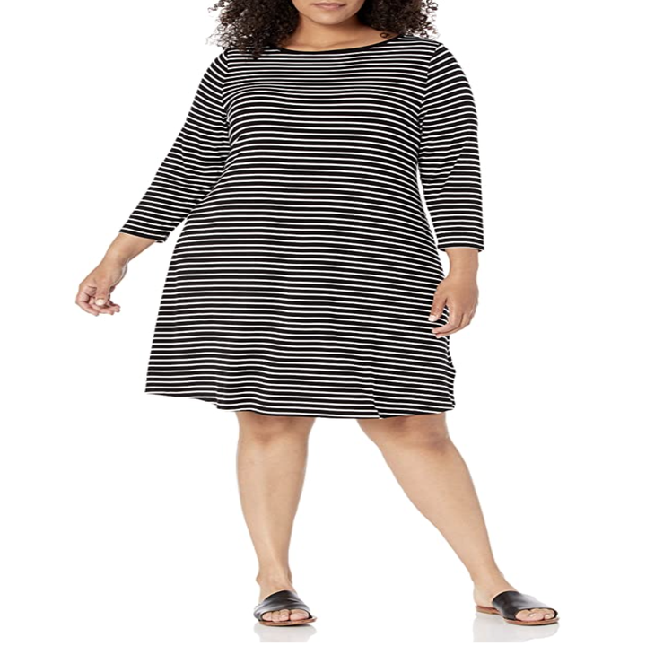 a model in a quarter-sleeve boatneck dress in black with white vertical thin stripes