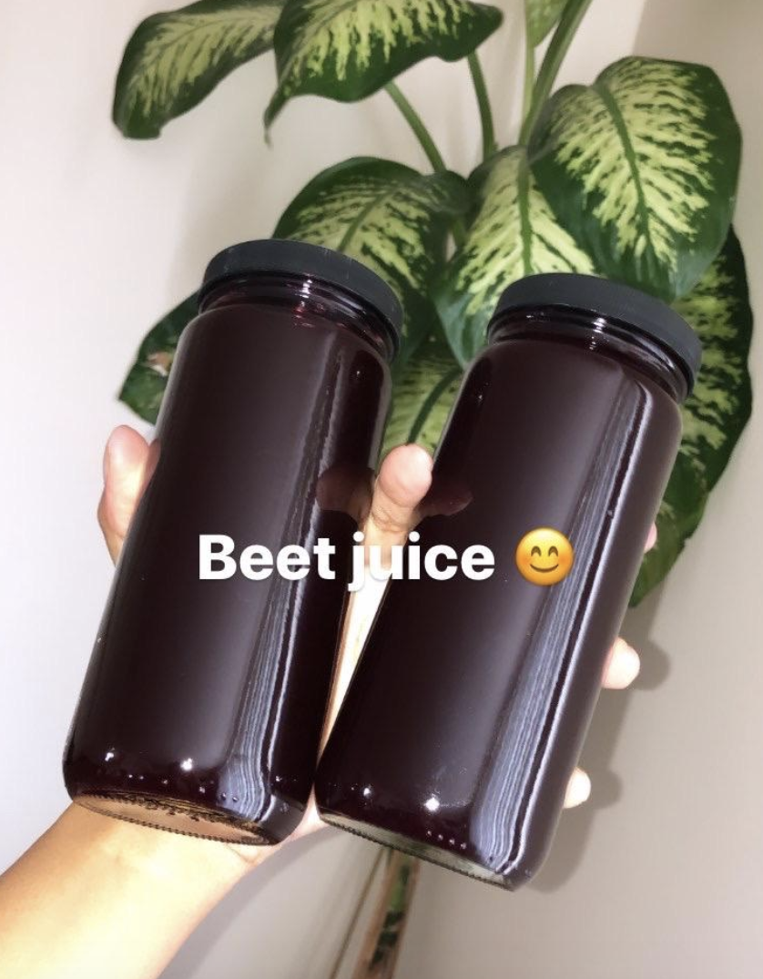reviewer holding two bottles with beet juice inside