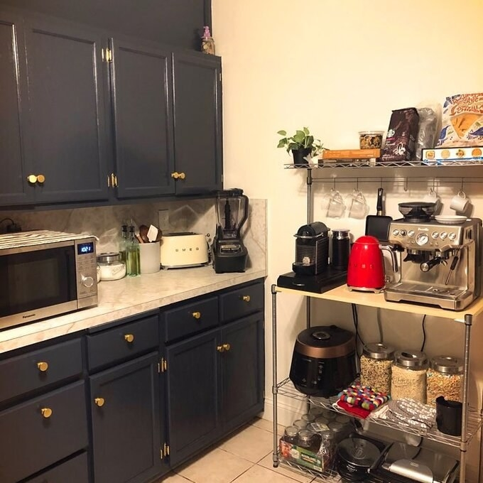 Reviewer's picture of the cart with two bottom shelves, a flat top, four hooks for mugs, and a top shelf that is storing their kitchen appliances