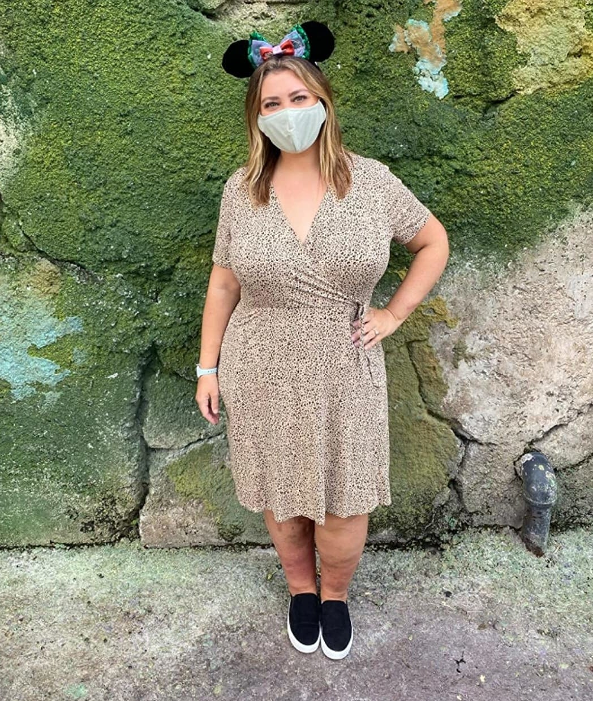a reviewer in a cheetah print dress at disney world