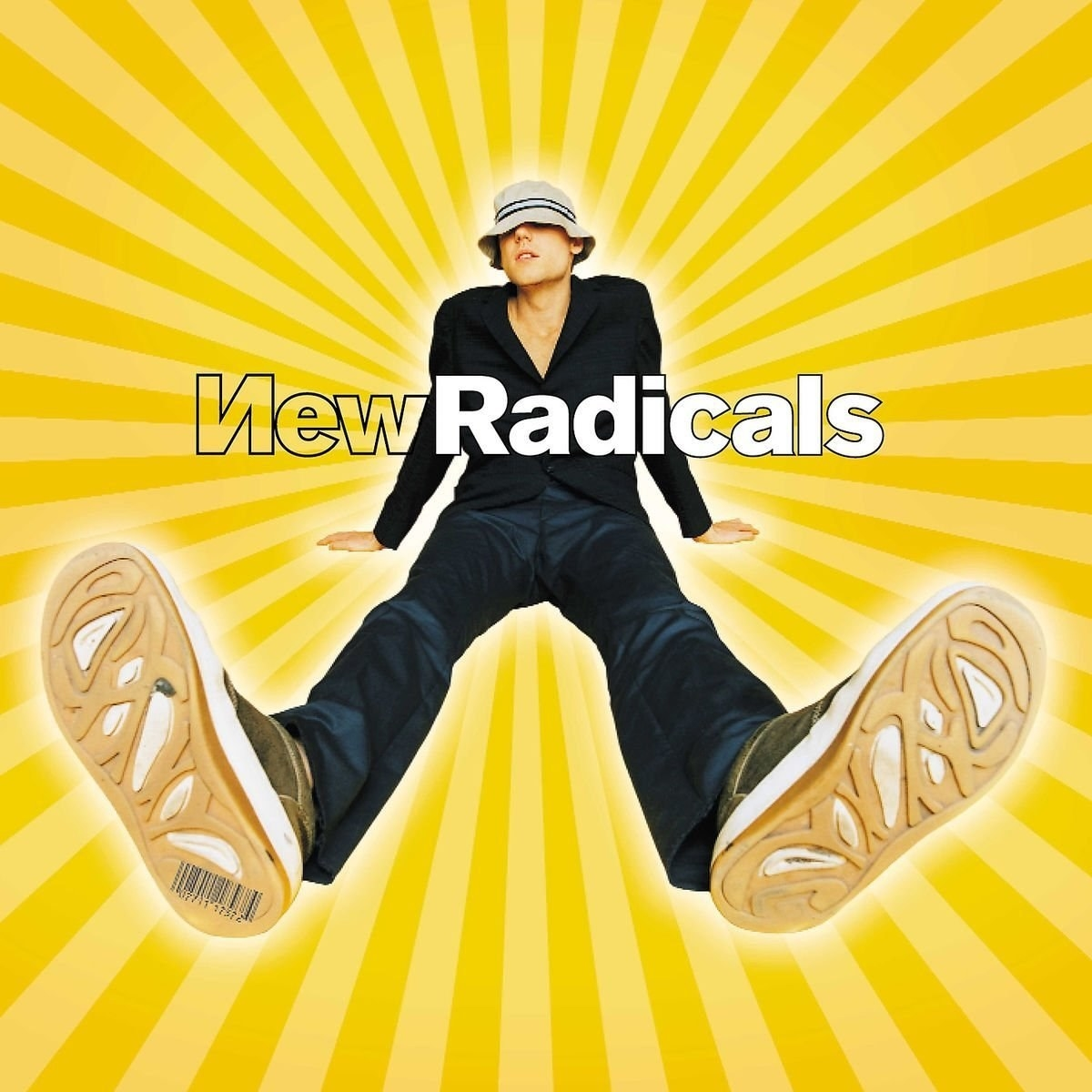 The New Radicals album cover featuring the lead singer wearing a bucket hat and sitting down with a yellow burst behind him