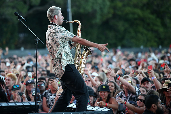 A man playing a saxophone to a massive crowd