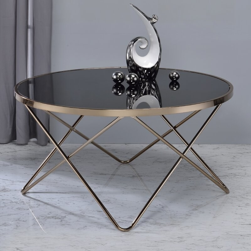 a black glass coffee table with brass legs and a brass rim