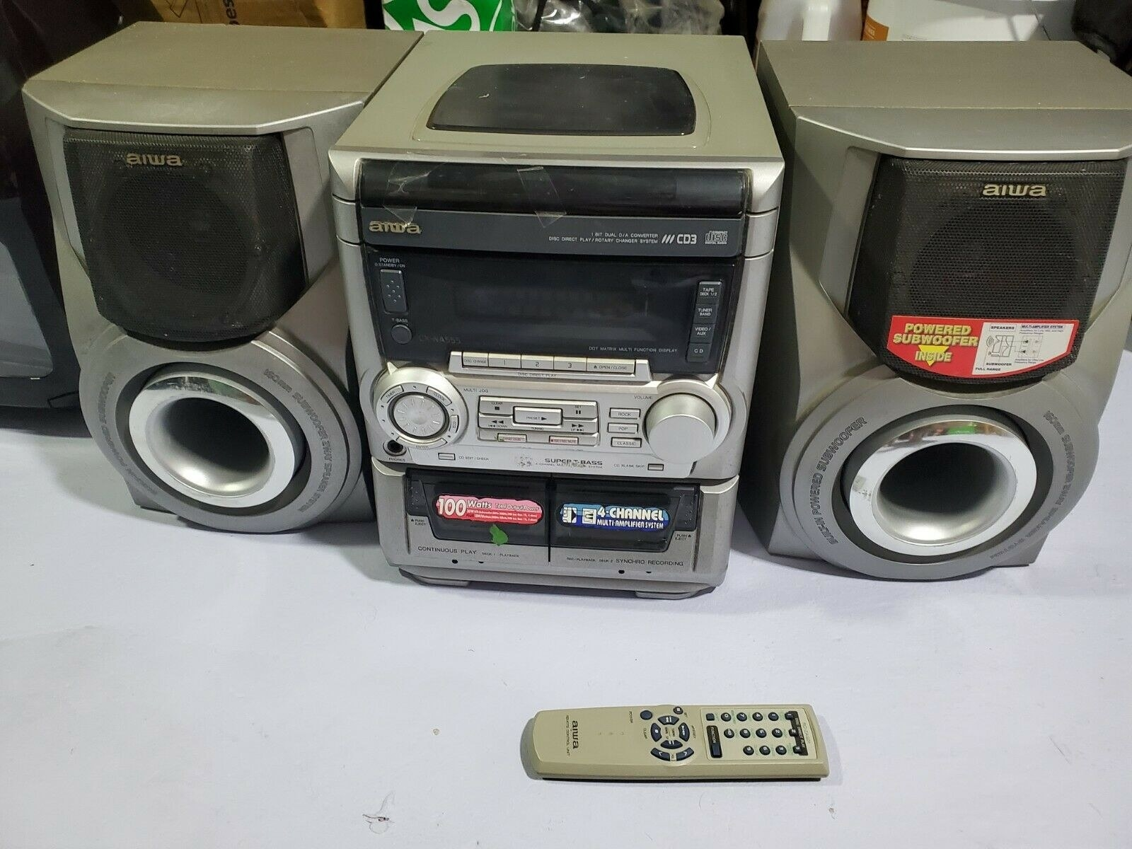 A 3-CD boombox with a remote next to it