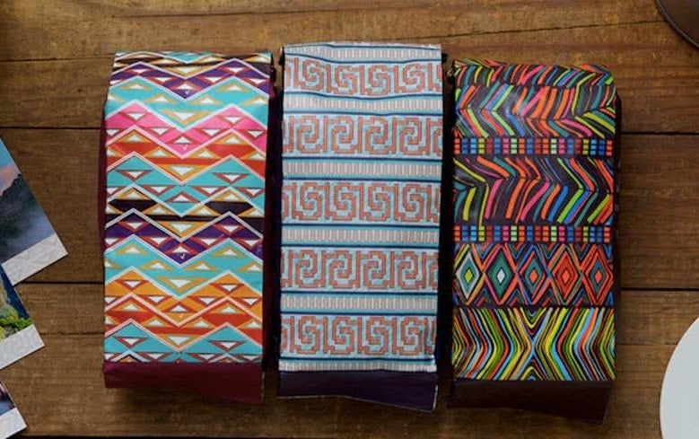 Three bags of coffee beans with various bright patterns