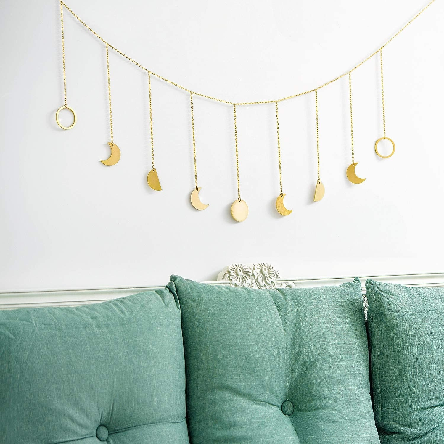 Moon phases in gold colored pressed metal hanging from delicate chains