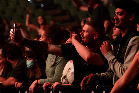 A man taking a selfie at a concert