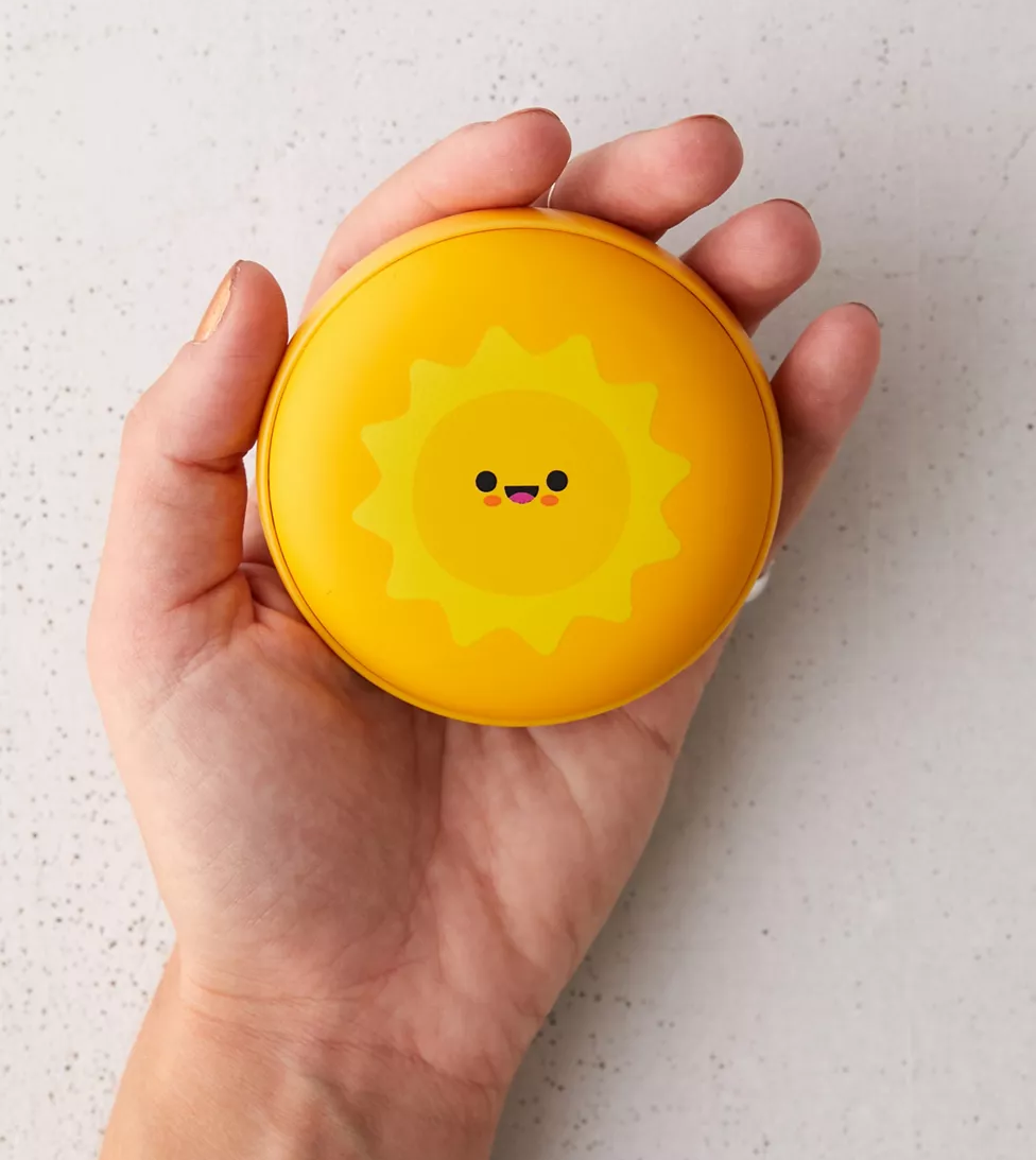 hand holds hand warmer with sun on it