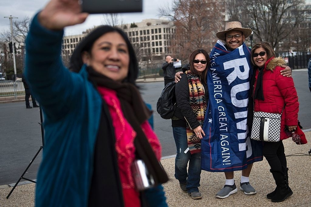 "Two women take a picture with the support wrapped in a ""Trump"" flag"