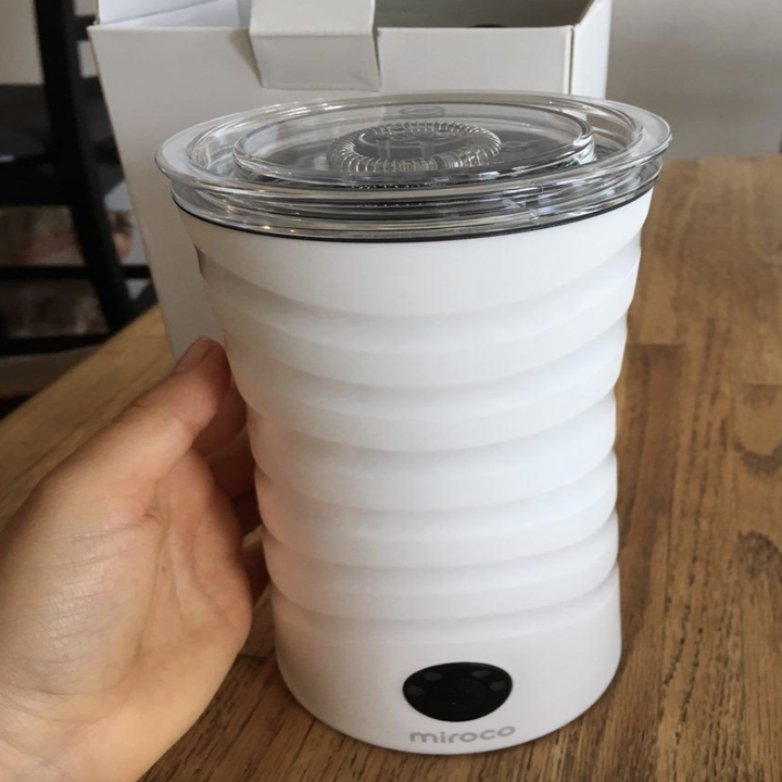reviewer holding the white frother