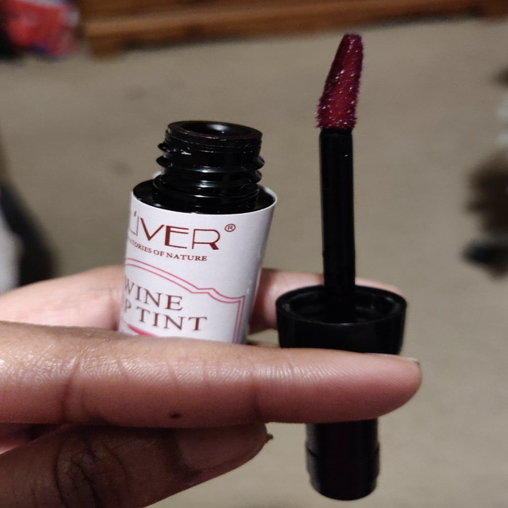 reviewer holding up the application wand of the lipstick