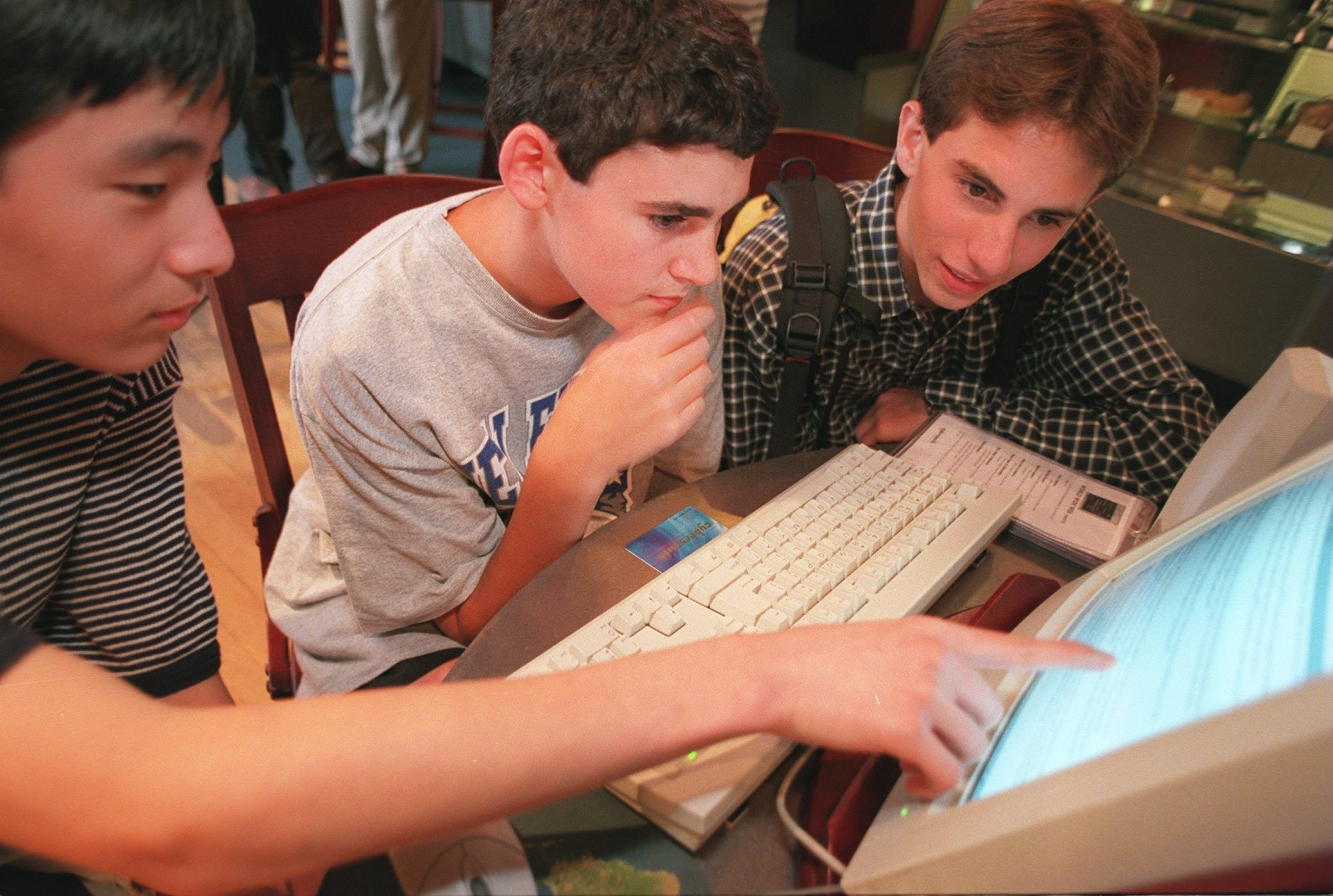 Three teens sitting in front of a desktop computer