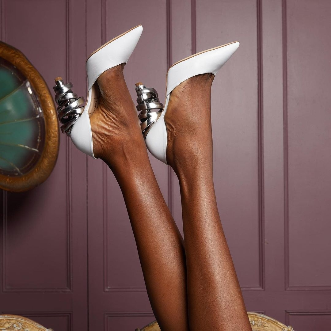 White pumps with silver metal wrapped around the heel