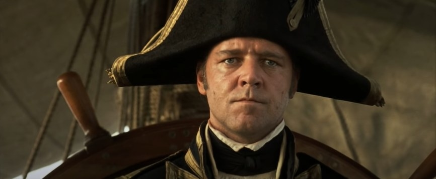 Russell Crowe wearing a captain's hat on a ship.