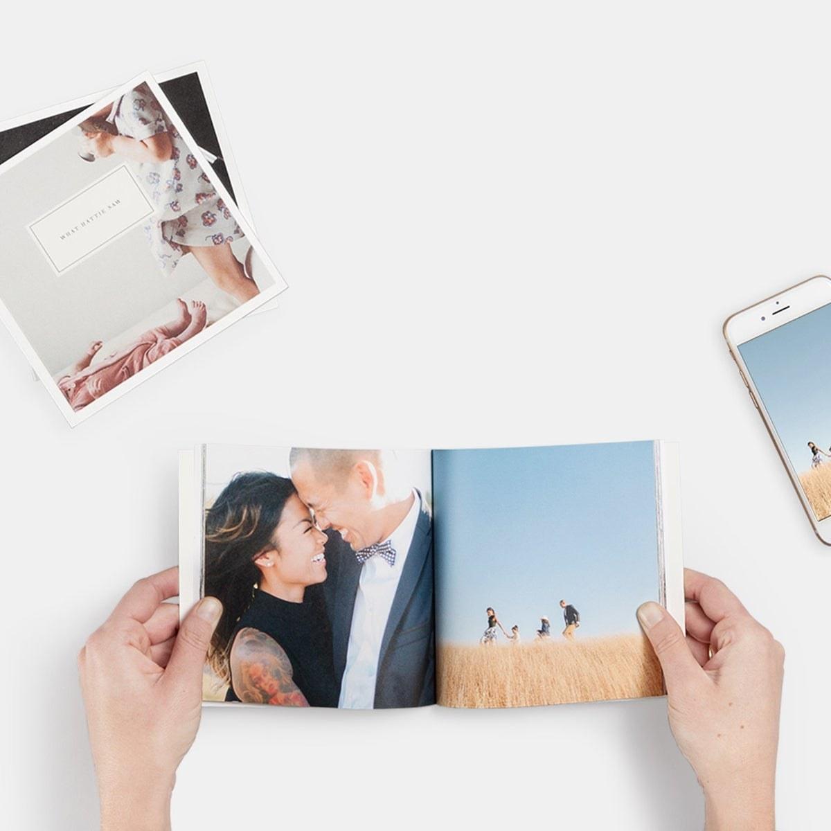 a model holding a small square photo album