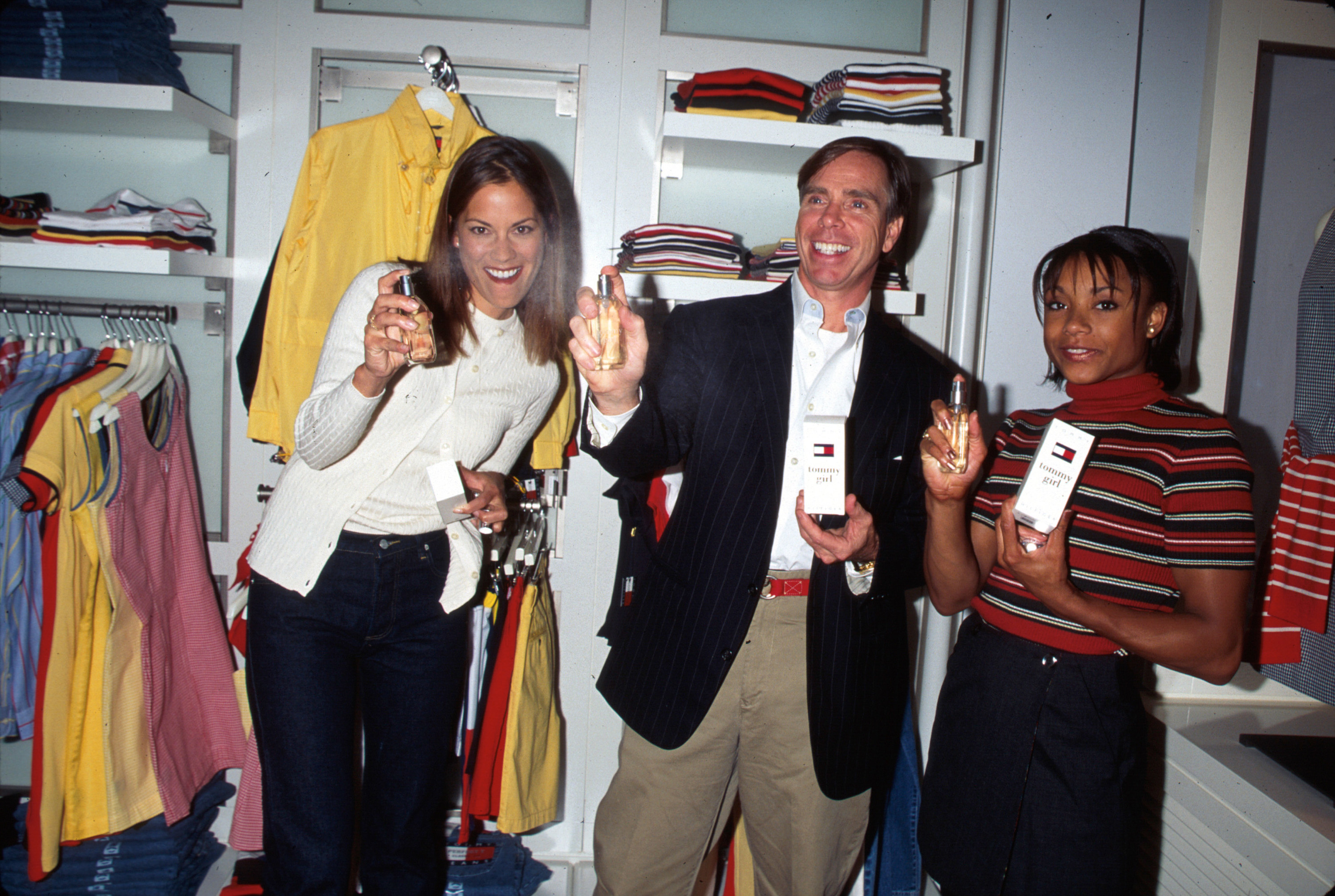 Tommy Hilfiger and two models spraying Tommy Girl perfume inside a store