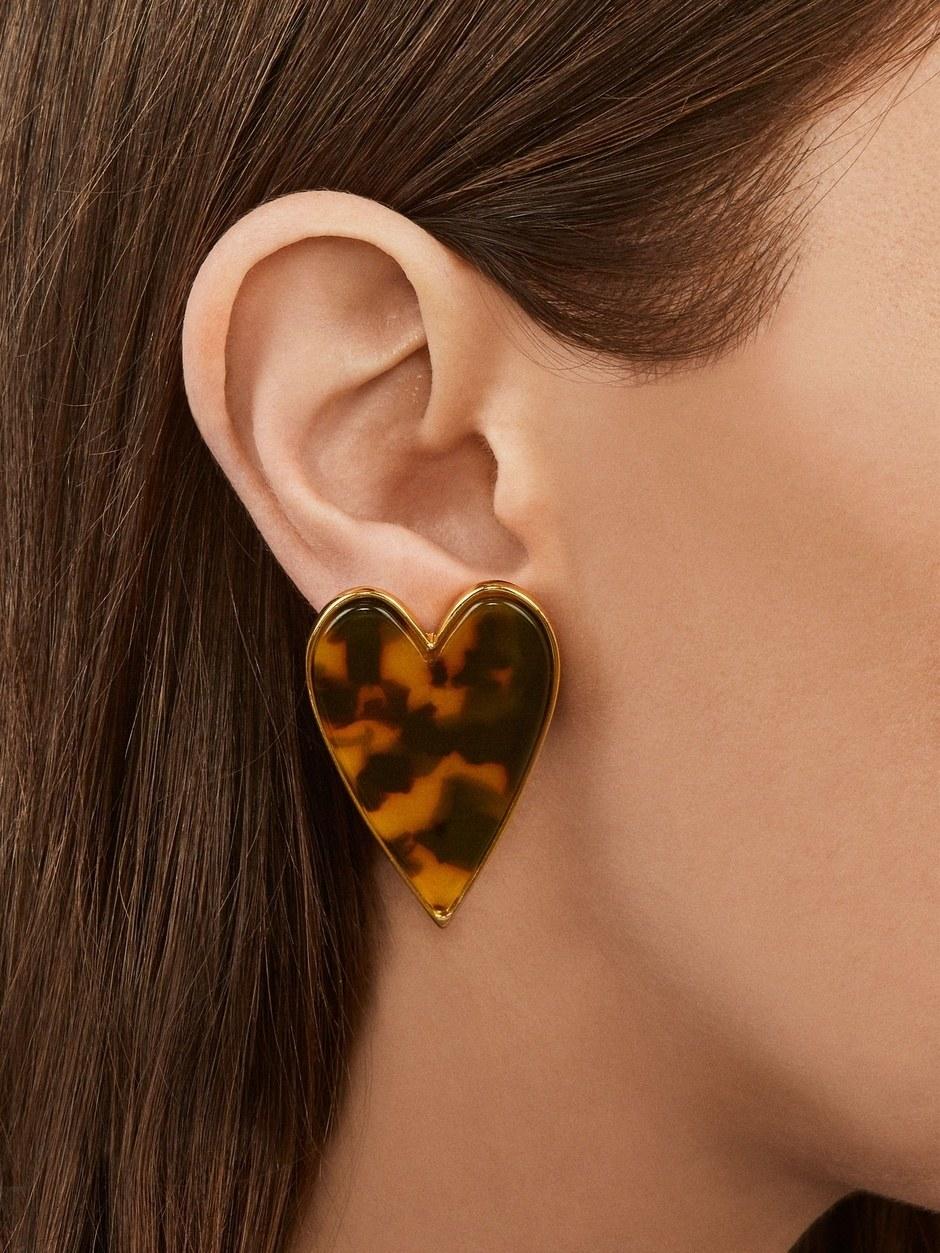 a model wearing heat shaped tortoise shell earrings