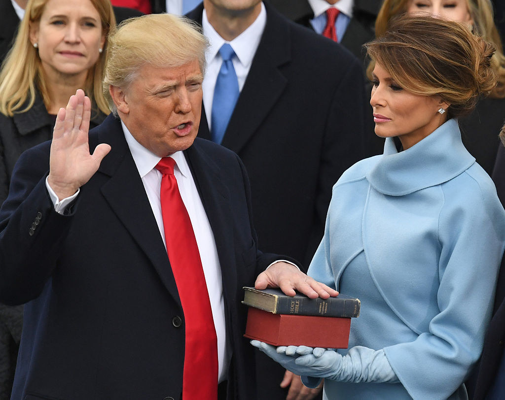 Trump taking the oath of office with his hand on a Bible being held by his wife Melania