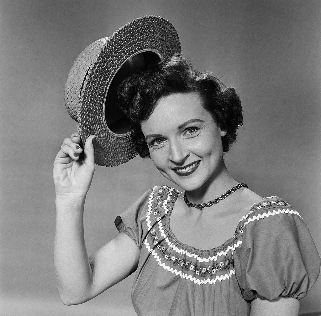 Betty posing for a photo by smiling and tipping her hat