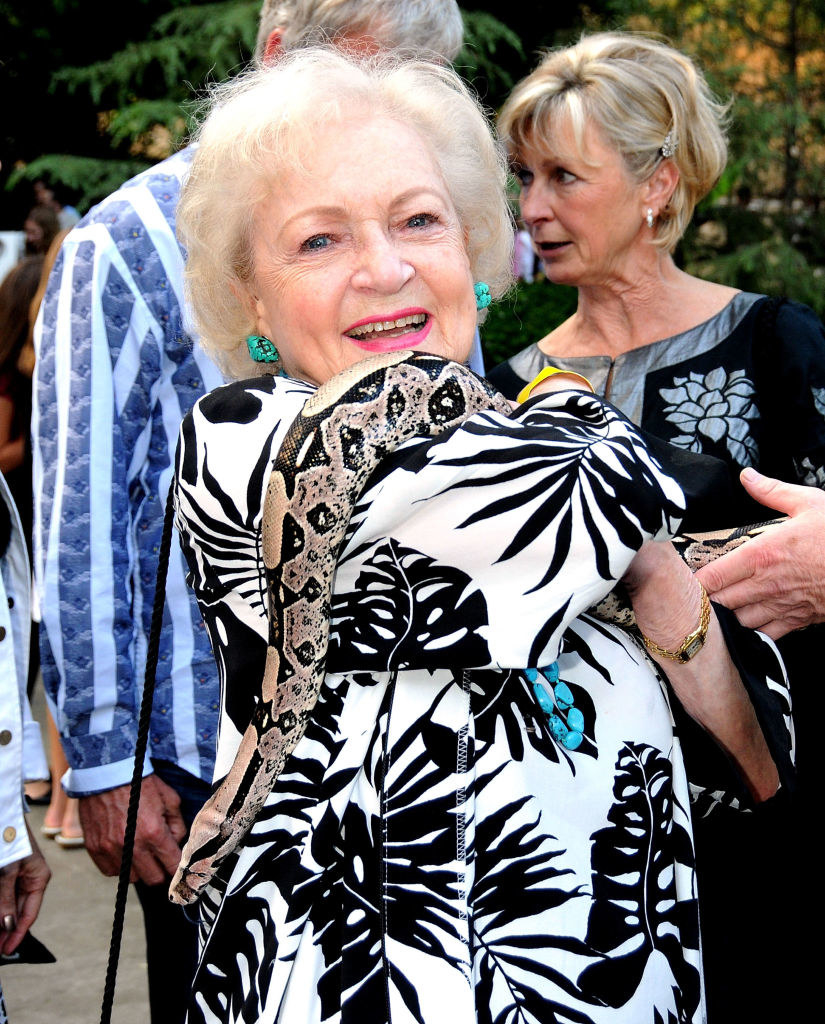 Betty White fearlessly holding a snake over her shoulder