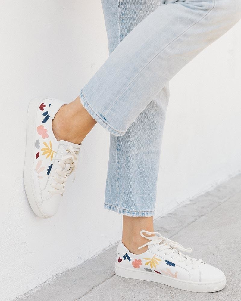 model wearing the lace-up sneakers in white with embroidered leaves in different colors on either side