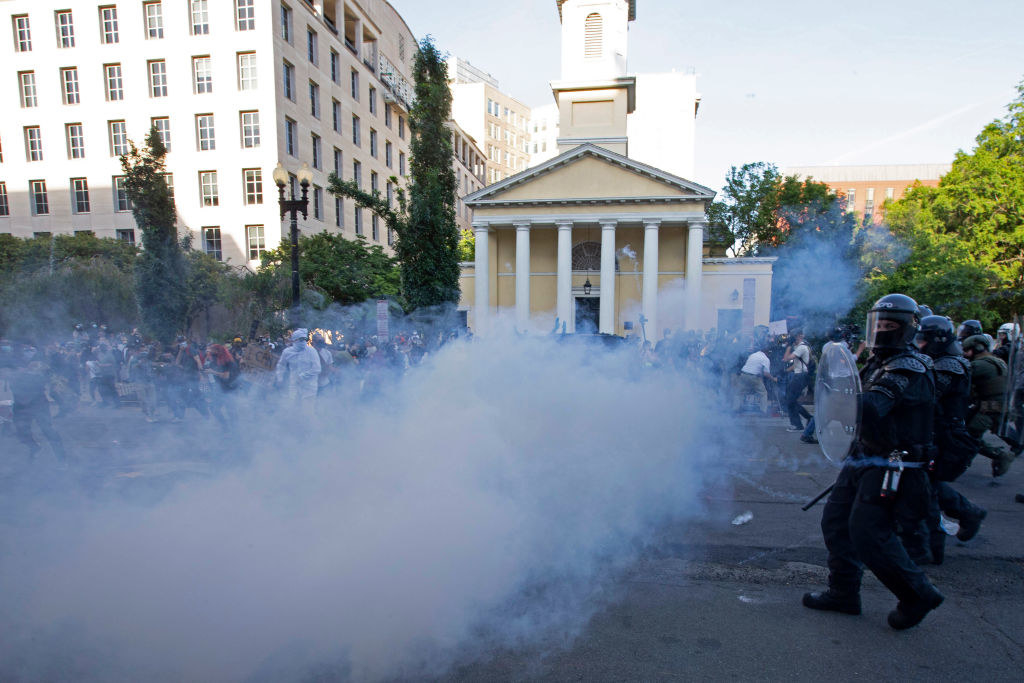 Smoke fills the air in front of security officials in riot gear as they try to disperse a crowd