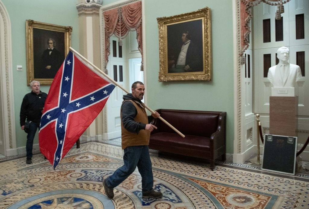 A man holding a Confederate flag strolls through the Capitol halls