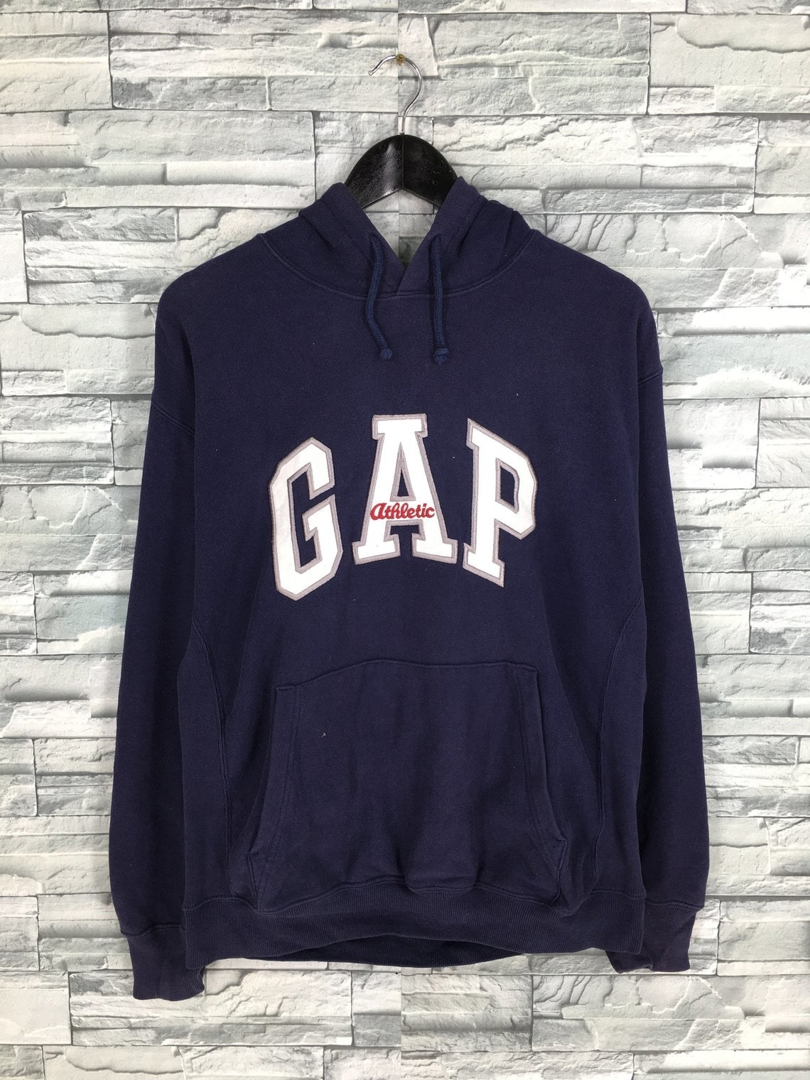 A navy Gap hoodie with Gap athletic embroidered on the chest