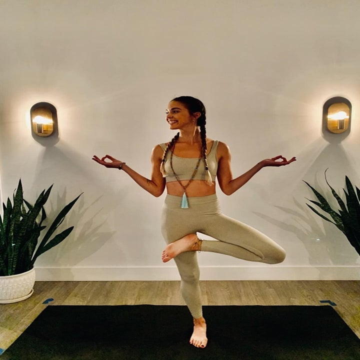 reviewer wearing the full-length leggings and scoop-neck sports bra in tan