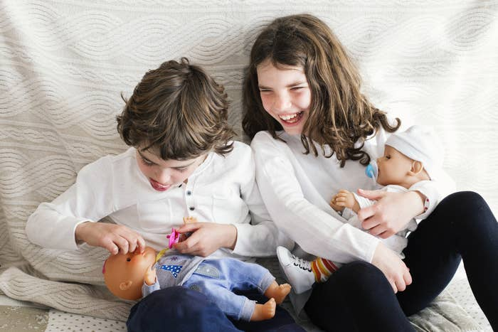 A boy and a girl playing with baby dolls