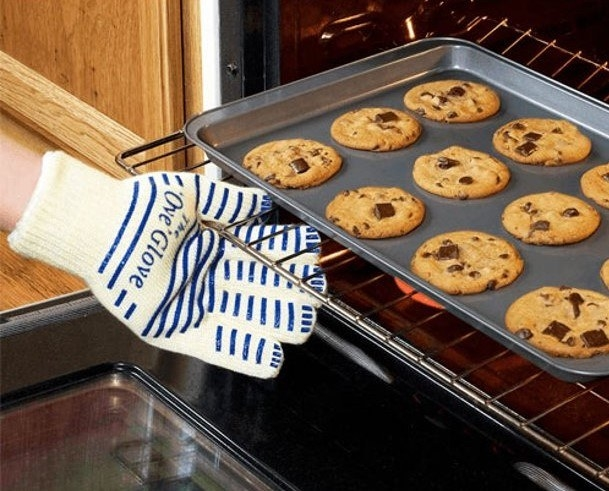 A person wearing the glove retrieving cookies from the oven