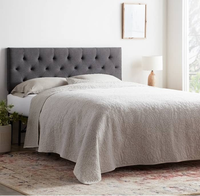 Gray fabric upholstered headboard on bed