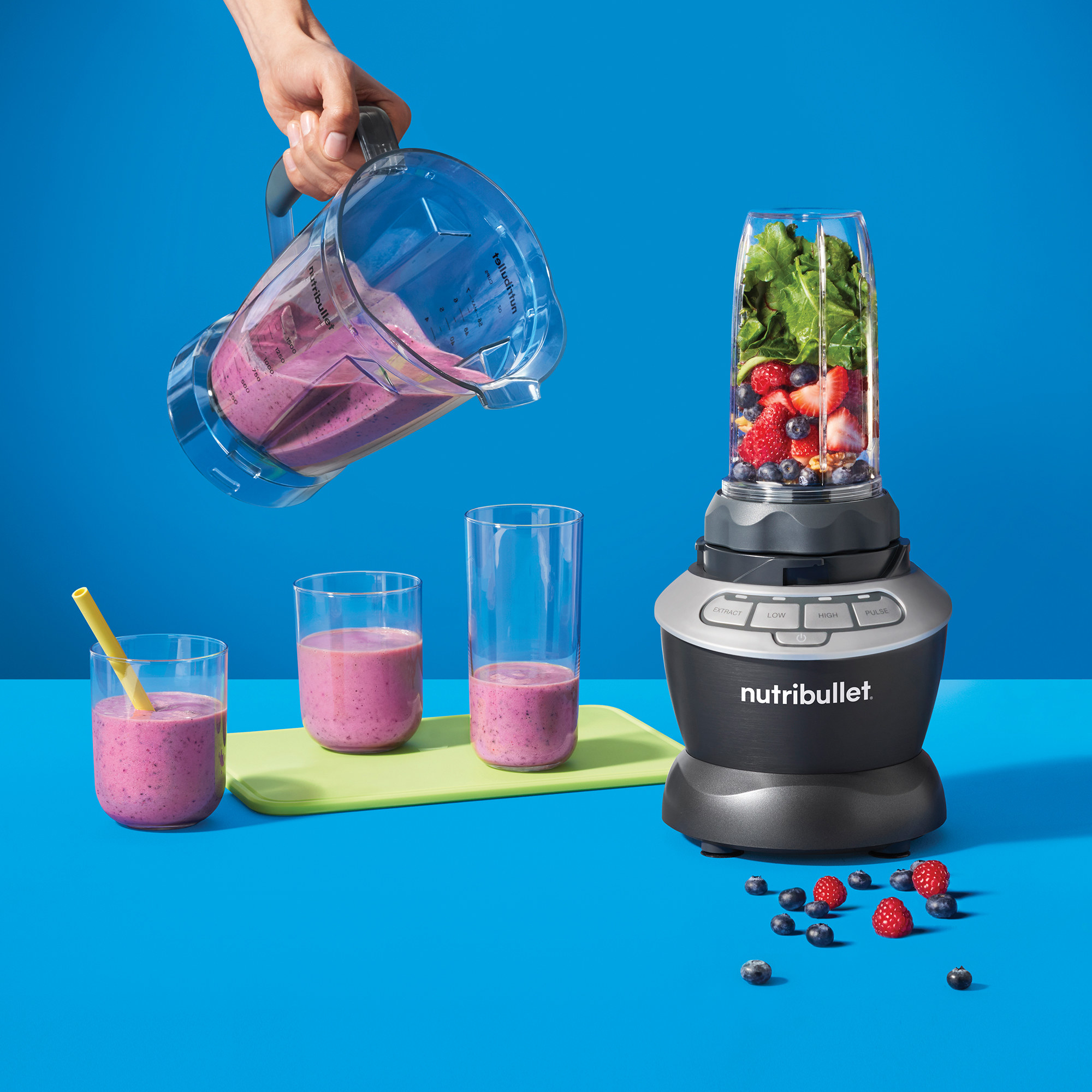 The blender shown with the single-serving cup on it, and someone pouring a smoothie out of the larger container
