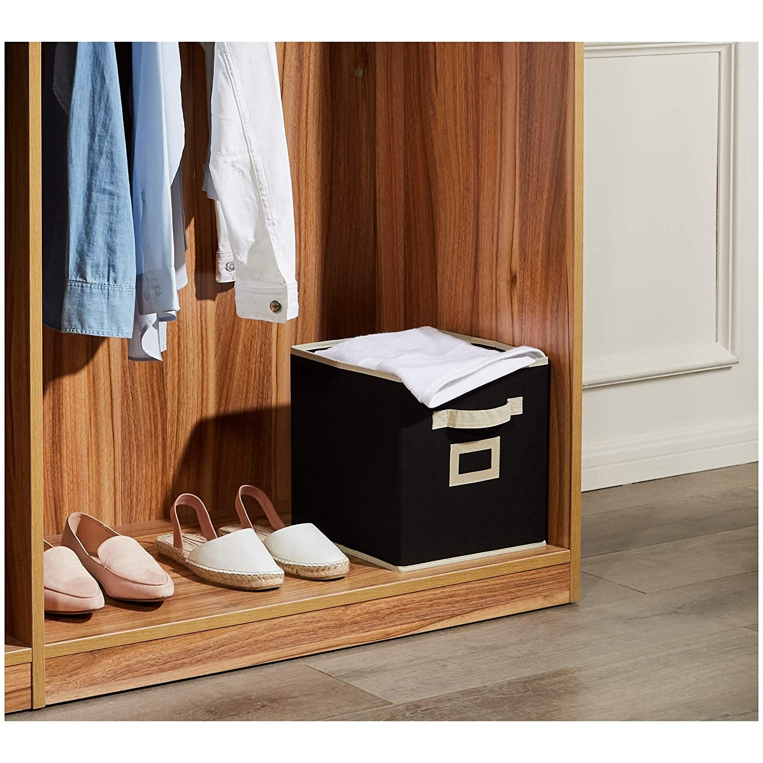 A black storage box in the corner of a closet