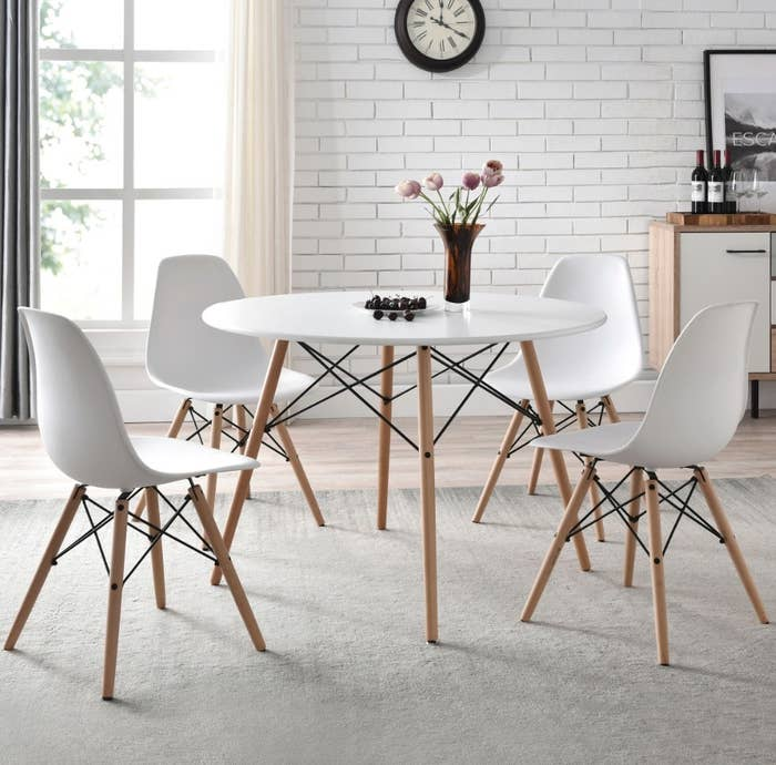 Round white table with wooden legs and matching white chairs