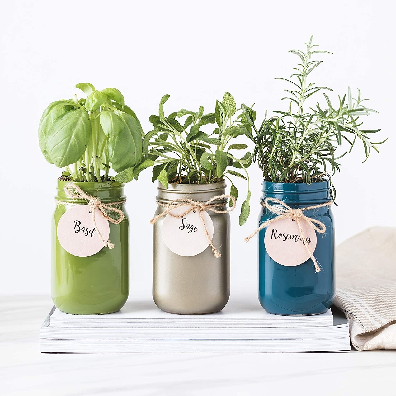 Three jars of herbs on top of a magazines