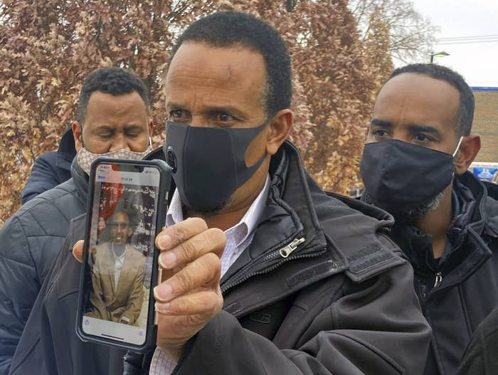 Bayle Gelle holds a phone with a photo of his 22-year-old son, Dolal Idd
