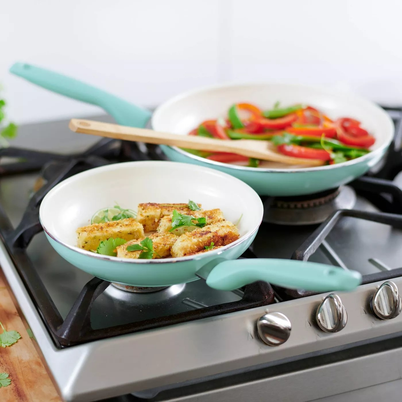 The two pans on stove top with cooked food inside