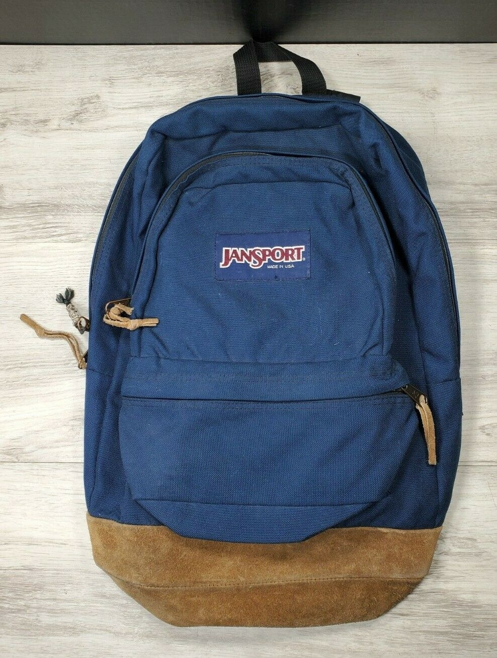 A navy JanSport backpack with a suede bottom