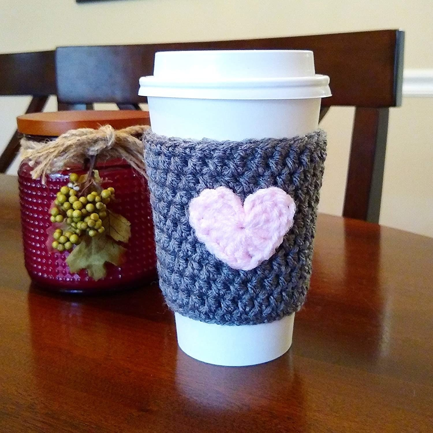 a white disposable coffee cup with a gray knitted sleeve that has a light pink heart in the center