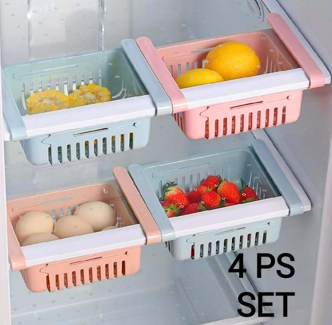 Four storage boxes in multiple colours installed in a fridge with various food items in them.