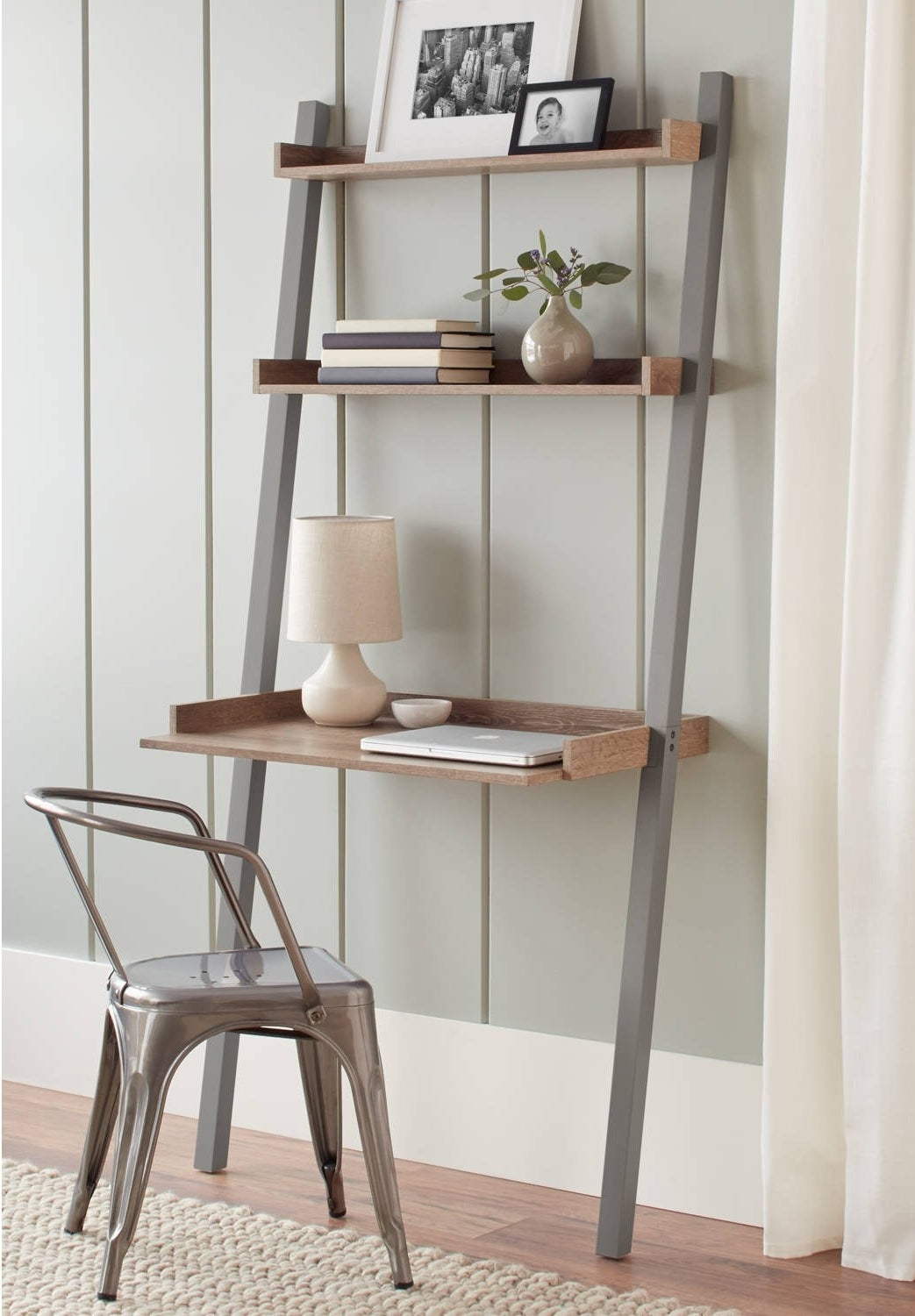 The gray leaning desk positioned against a wall in a home office
