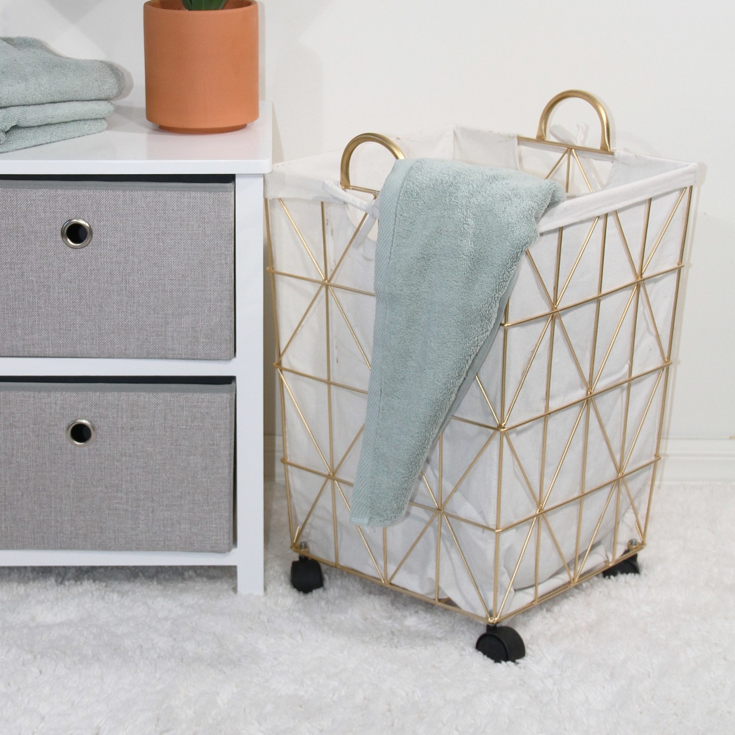 The gold hamper on black wheels in a laundry room