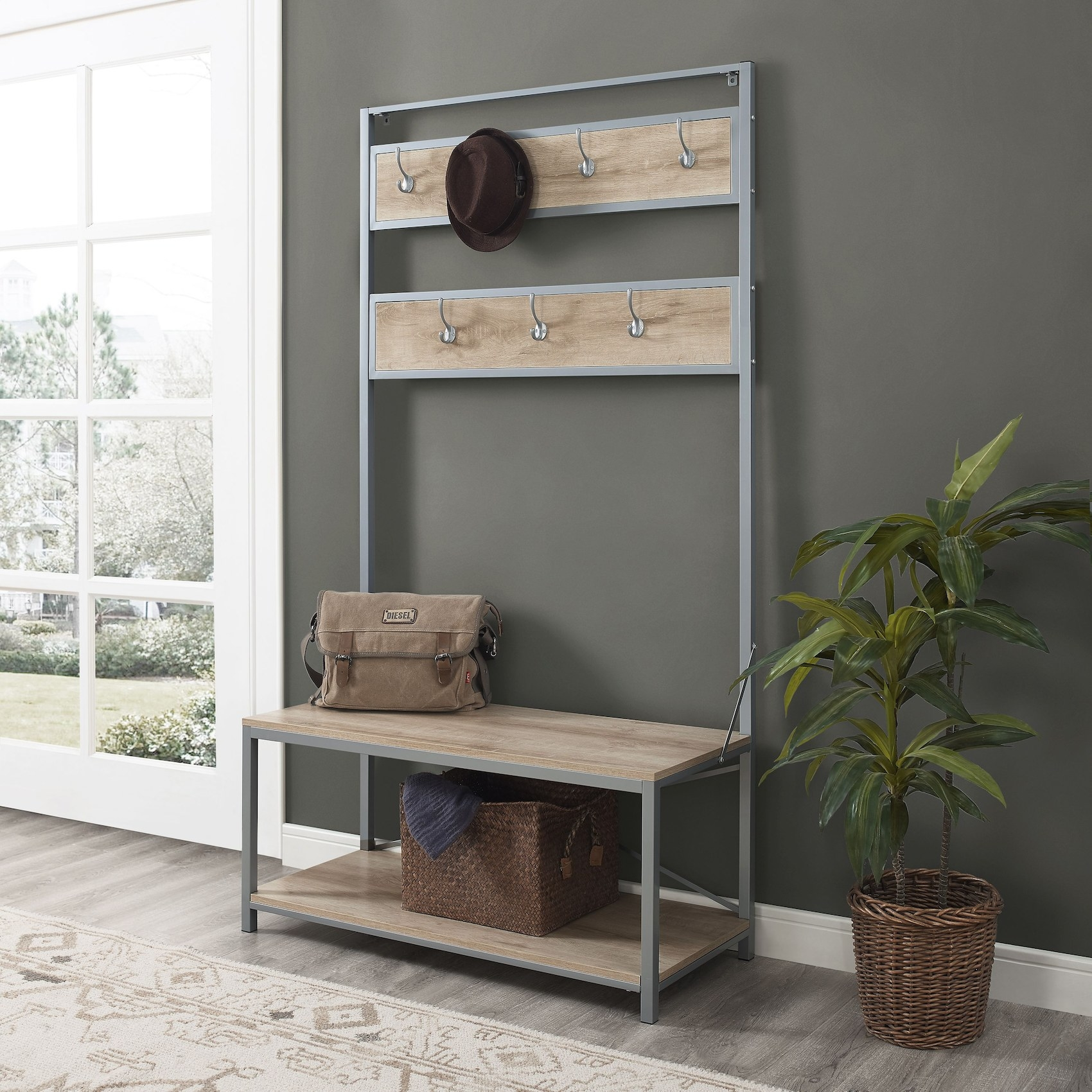 The wood and metal hall tree with coat hooks, a bench and storage in an entryway